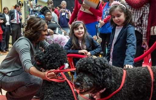 Michelle Obama, with Sunny (center) and Bo (left), visit with children.
